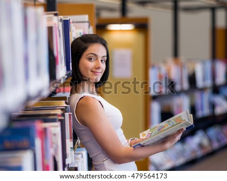 Happy female student at the library