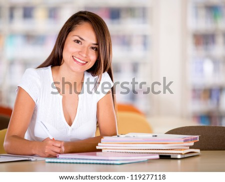 Happy female student at the library smiling - stock photo