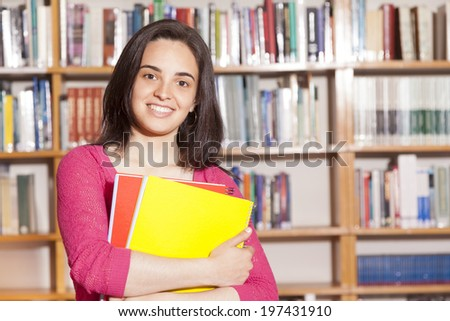 Happy female student holding books at the library - stock photo