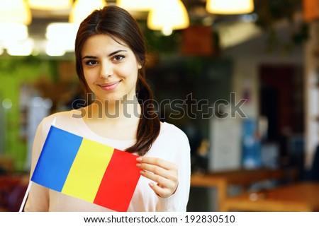 Happy female student holding flag of Romania - stock photo