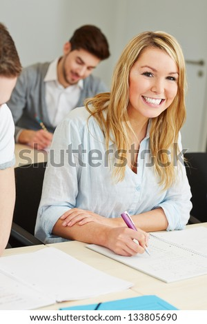 Happy female student in college class studying - stock photo