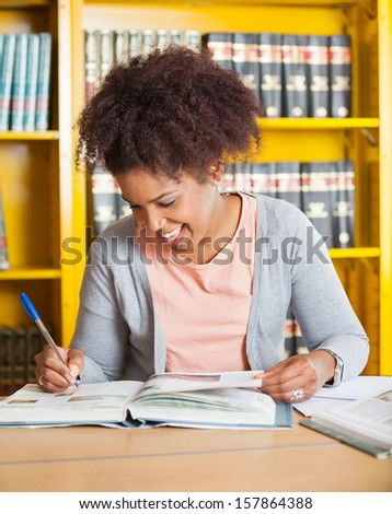 Happy female student writing in book at university library