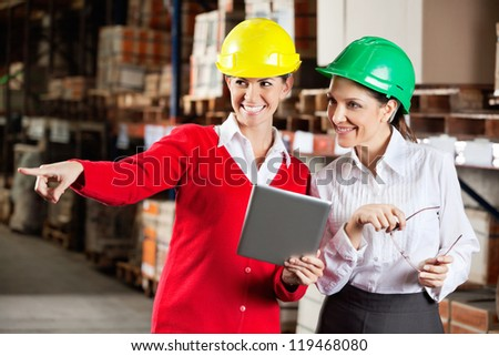 Happy female supervisor with digital tablet showing something to colleague in warehouse - stock photo