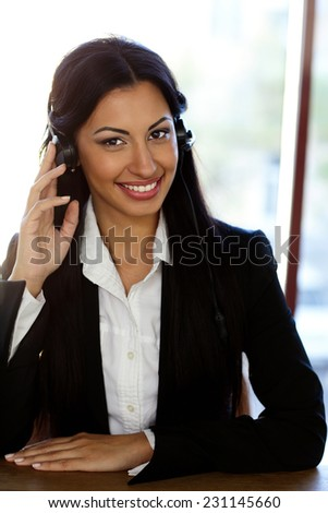 Happy female support phone operator in headset at workplace - stock photo