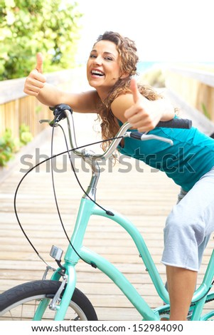 Happy Female Taking A Break On Boardwalk With Bicycle Smiling Giving Thumbs up - stock photo