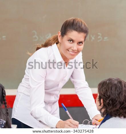 Happy female teacher checking students homework at school. - stock photo