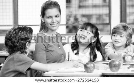 Happy female teacher in a multi ethnic elementary classroom. - stock photo