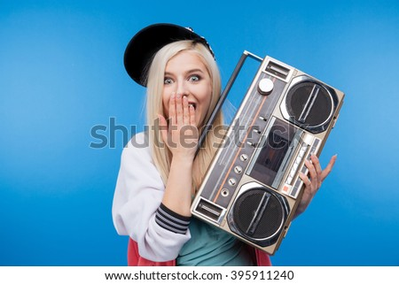 Happy female teenager holding retro boom box on blue background - stock photo