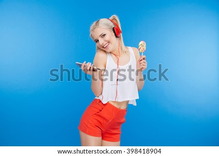 Happy female teenager listening music on smartphone and holding lollipop over blue background
