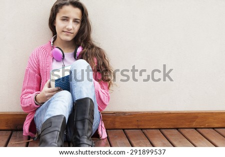Happy female teenager student with book and headphones