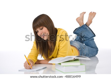 Happy female teenager write homework lying down with book on white background