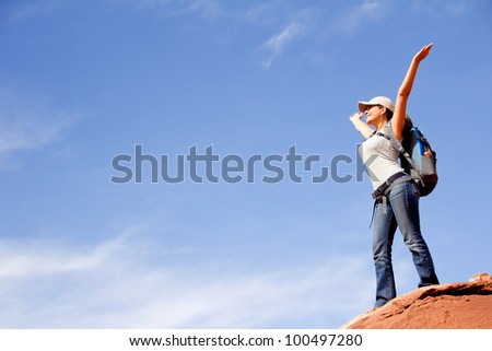 Happy female tourist at the top of a mountain with arms up - stock photo