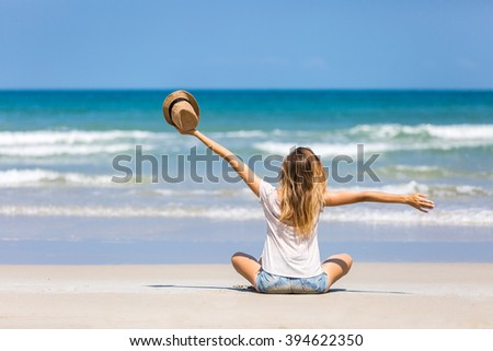 Happy female tourist on a beautiful beach with white sand and turquoise water - stock photo