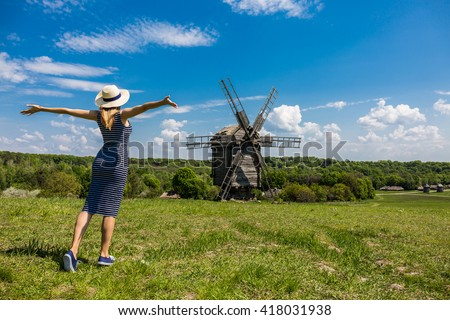 Happy female tourist watching authentic windmill, Eco Tourism concept - stock photo