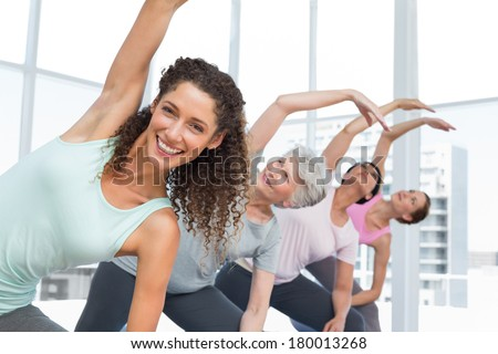 Happy female trainer with class stretching hands at yoga class - stock photo