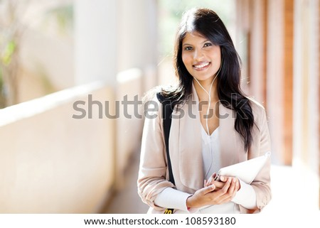 happy female university student using tablet computer listening music on campus
