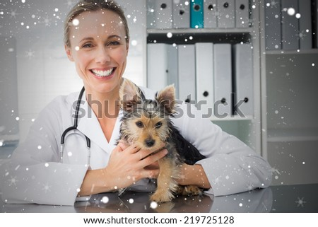 Happy female veterinarian holding puppy against snow
