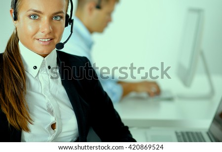 Happy female wearing headset and sitting on the desk - stock photo