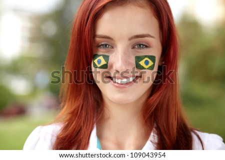 Happy female with Brazil flags on her cheeks - stock photo