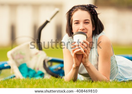 Happy female with coffee cup lying on grass acting cheerful and relaxing outdoors - stock photo
