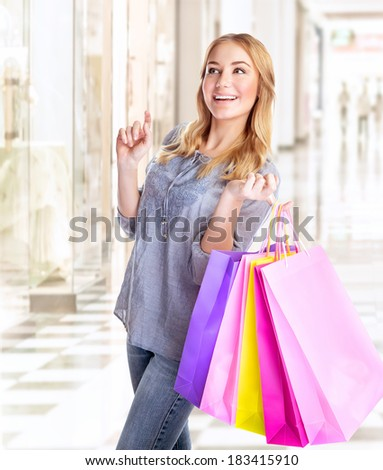 Happy female with shopping bags in retail store, enjoying purchase in the mall, excited consumer with colorful paper bags, conception of pleasure - stock photo