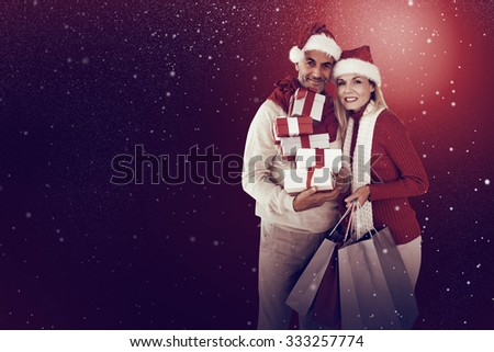 Happy festive couple with gifts and bags against snow - stock photo