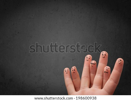 Happy finger smileys faces on hand with empty copy space dark background