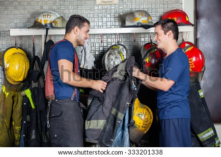 Happy firefighters looking at each other while holding jacket in fire station - stock photo