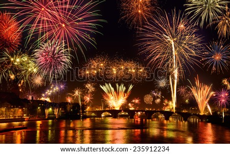 Happy fireworks display in the city, with lots of colorful bangs rising high into the night sky and brightly reflected on the river - stock photo