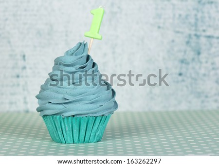 Happy first birthday cupcake with candle number 1