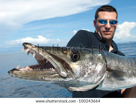 Happy  fisherman holding a giant barracuda - Close up on barracuda teeth - stock photo