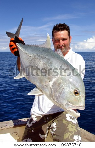 Happy  fisherman holding a trevally jack - stock photo