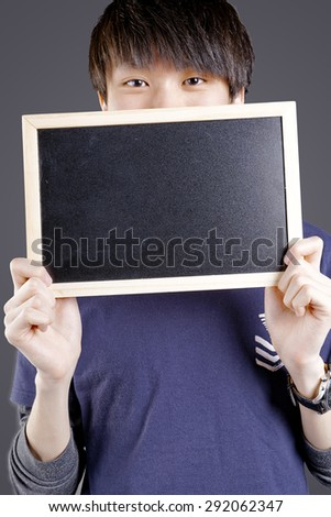 happy fit asian chinese man holding a black board with sport cloth