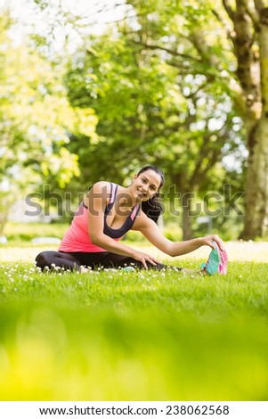 Happy fit brunette stretching on the grass in the park - stock photo