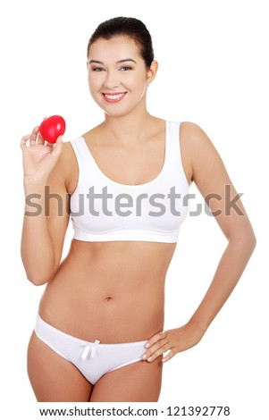 Happy Fit female in white sport underwear with red heart shaped toy