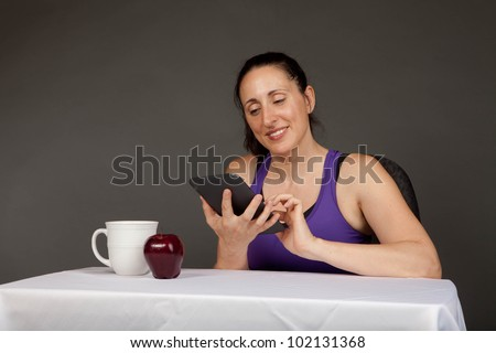 Happy fit girl after a workout sitting with an electronic reader and a snack - stock photo