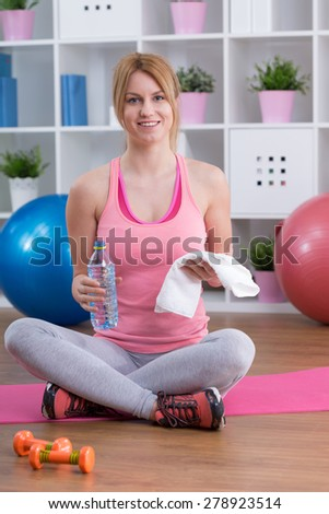 Happy fit girl holding water and towel for exercises