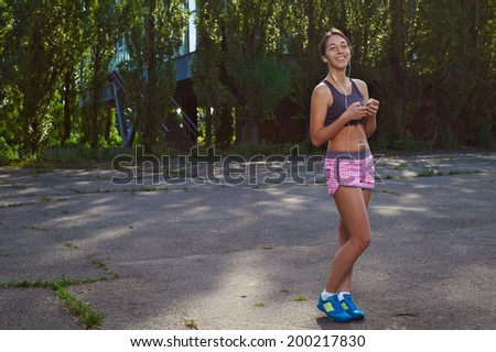 happy fit girl posing in the park with her phone