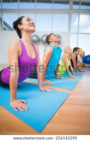 Happy fit people doing the cobra pose in fitness studio - stock photo