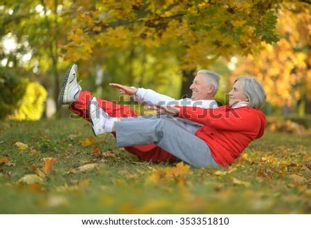 Happy fit senior couple exercising in autumn park - stock photo