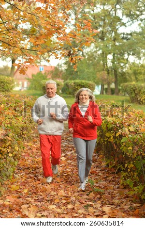 Happy fit senior couple jogging in autumn park - stock photo