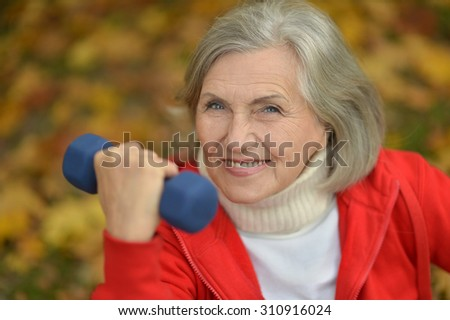 Happy fit senior woman exercising in autumn park - stock photo