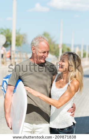 Happy fit tanned middle-aged couple going surfing walking along a sunny street arm in arm carrying a surfboard - stock photo