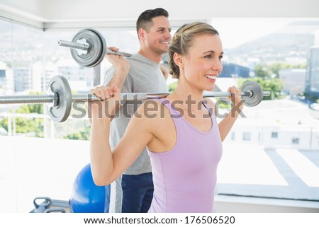 happy fit woman and man lifting barbells in the exercise room - stock photo