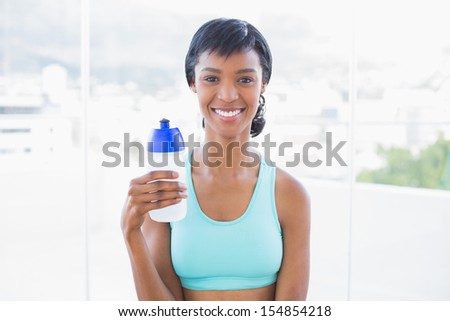 Happy fit woman holding a bottle of water in a living room - stock photo