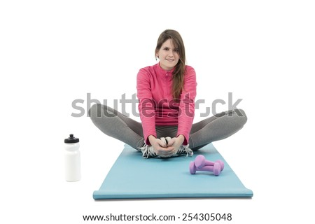 Happy fit woman sitting on her exercise mat against a white background - stock photo