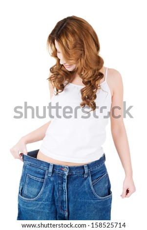 Happy fit woman with big pants, showing how much weight she lost. - stock photo