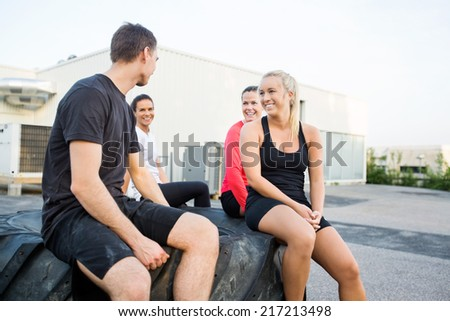 Happy fit young friends relaxing on tire after workout outdoors - stock photo
