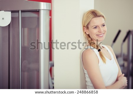 Happy Fit Young Woman Leaning on White Post Inside the Fitness Gym While looking Afar. - stock photo