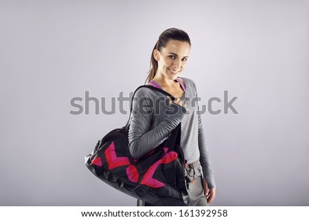 Happy fit young woman with gym bag standing ready for fitness exercise. Young caucasian female going for gym looking at camera smiling. Representing a healthy lifestyle. - stock photo